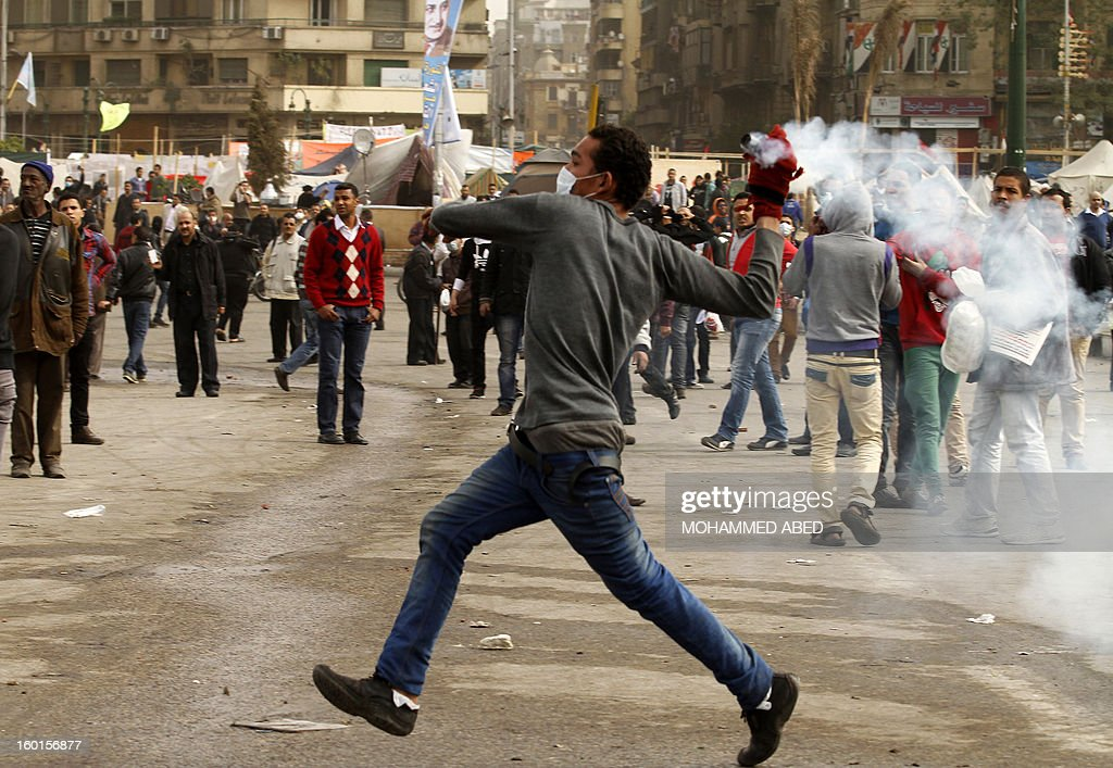 An Egyptian protester prepares to throw back a tear gas canister fired by riot policemen during clashes near Cairo's Tahrir Square on January 27, 2013. Clashes killed at least 31 people in Egypt's Port Said as violence raged in several cities including the capital following death sentences passed on 21 football fans after a riot.