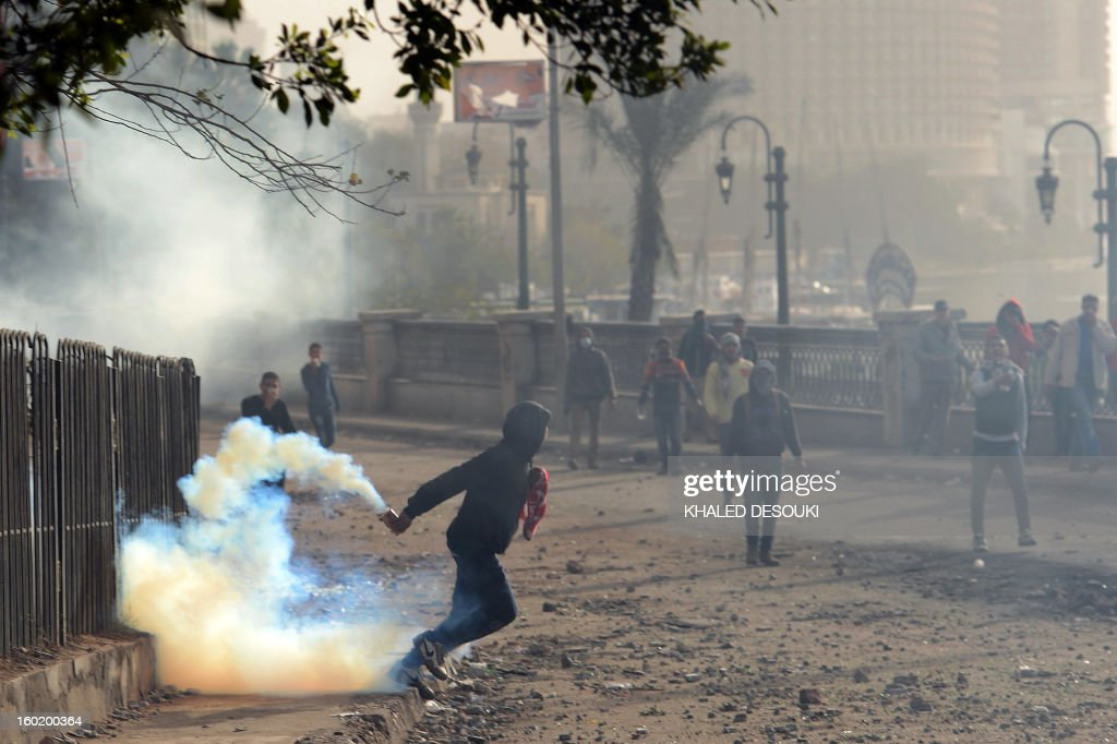An Egyptian protester prepares to throw back a tear gas canister fired by riot police during clashes near Cairo's Tahrir Square on January 27, 2013. Clashes killed at least 31 people in Egypt's Port Said as violence raged into the early hours in several cities including the capital following death sentences passed on 21 football fans after a riot.