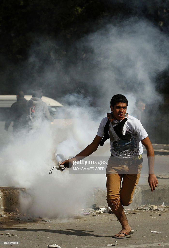 An Egyptian protester prepares to throw back a tear gas canister fired by riot police during clashes near Cairo's Tahrir Square on January 28, 2013. Egypt's cabinet approved a draft law that would allow President Mohamed Morsi to deploy the armed forces on the streets 'to participate with the police in preserving security and protecting vital establishments.'