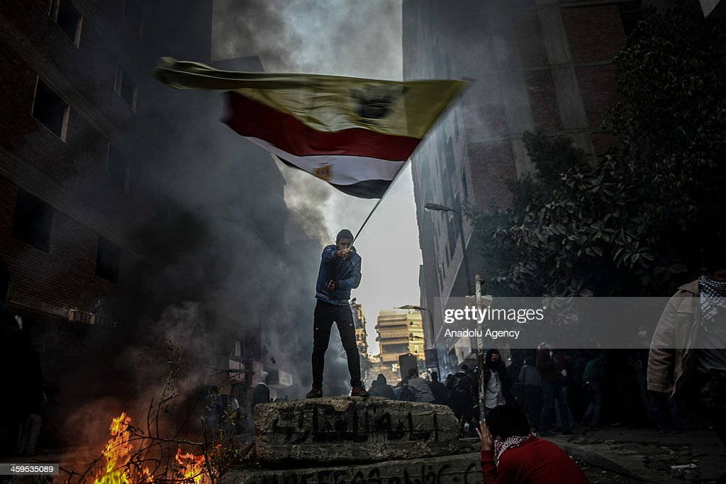 An Egyptian protester raises the flag during the clashes between Egyptian police and pro-democracy protesters after declaring the Muslim Brotherhood as a terrorist group in Alf Maskan district of Cairo, Egypt, December 27, 2013.