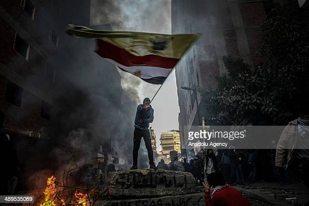 An Egyptian protester raises the flag during the clashes between Egyptian police and prodemocracy protesters after declaring the Muslim Brotherhood...