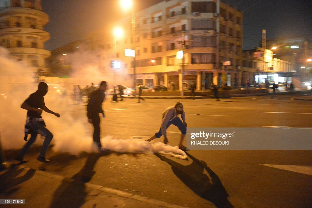 An Egyptian protester reaches for a tear gas canister fired by riot police at stone-throwing protesters in front of the presidential palace in Cairo, on February 11, 2013, during opposition held rallies to mark the second anniversary of former president Hosni Mubarak's overthrow.