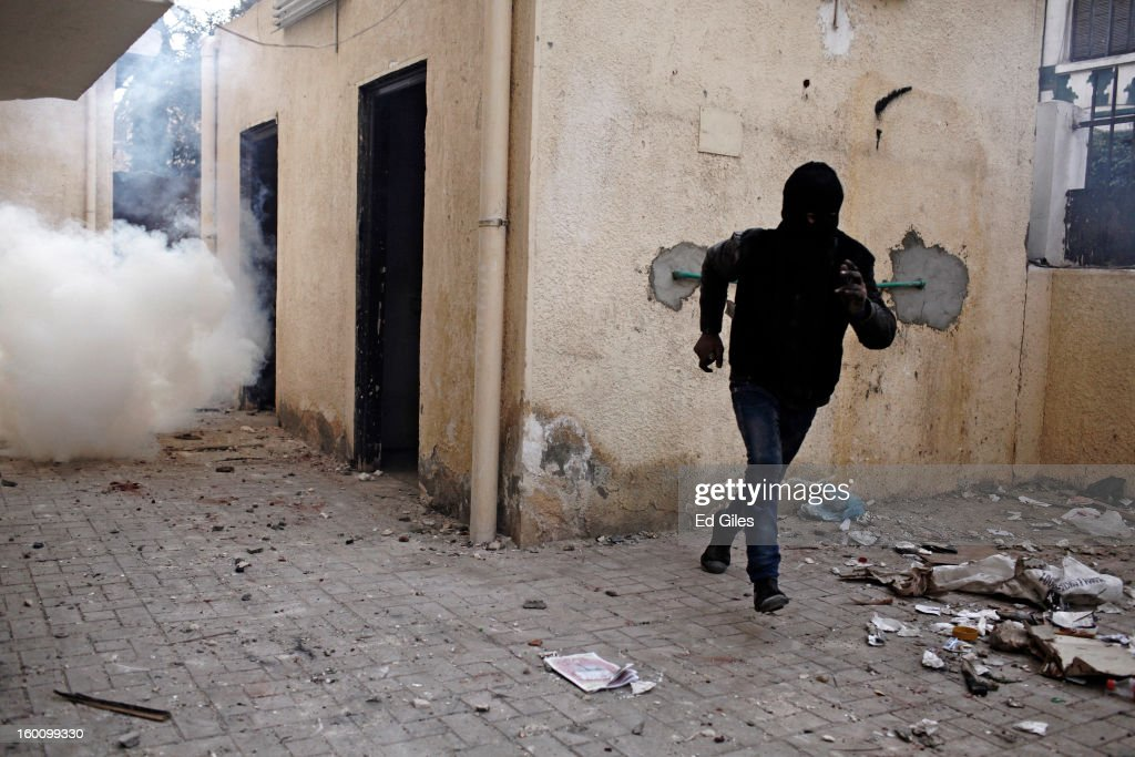 An Egyptian protester runs away from a cloud of tear gas fired by Egyptian riot police during a protest following the announcement of the death penalty for 21 suspects in connection with a football stadium massacre last year, on January 26, in Cairo, Egypt. Protests have continued across Egypt after a verdict was announced in a case over the deaths of more than seventy fans of Egypt's Al-Ahly football club in a stadium massacre on February 1, 2012, in the northern city of Port Said, during a brawl that began minutes after the final whistle of a match between Al-Ahly and opposing side, Al-Masry. 21 fans of the opposing side, Al-Masry, were given the death penalty in the court case, a verdict that must now be approved by Egypt's Grand Mufti. The verdict was handed down during a period of high tension across Egypt, one day after the second anniversary of the beginning of Egypt's 2011 revolution that overthrew former President, Hosni Mubarak.