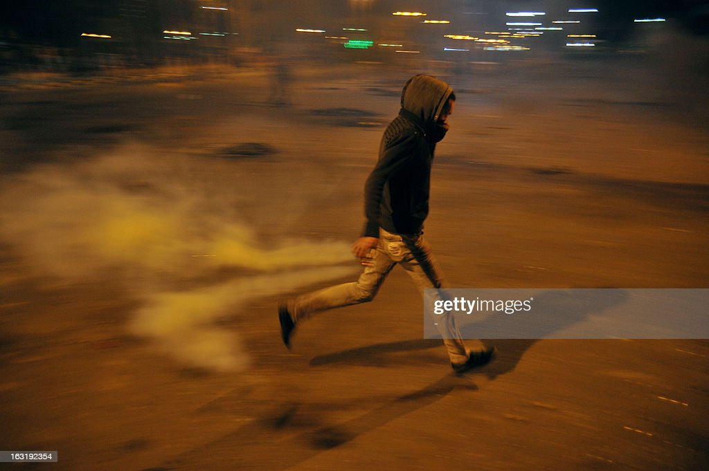 An Egyptian protester runs for cover as riot police fire tear gas during clashes in the Suez Canal city of Port Said late on March 5, 2013, as tenions rose between police and protesters in the restive Egyptian city, where six people were killed at the weekend.