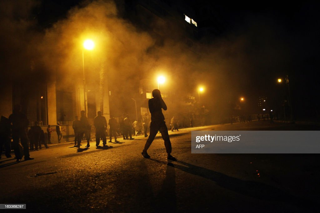 An Egyptian protester runs for cover from tear gas fired by riot police during clashes in Cairo, on March 8, 2013. Egyptian Interior Minister Mohamed Ibrahim sacked the riot police chief amid strikes by policemen who complained they are ill-equipped to confront protesters, state media reported.