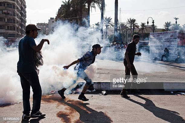 An Egyptian protester runs toward riot police holding a live tear gas canister during clashes near the United States Embassy and Cairo's Tahrir...
