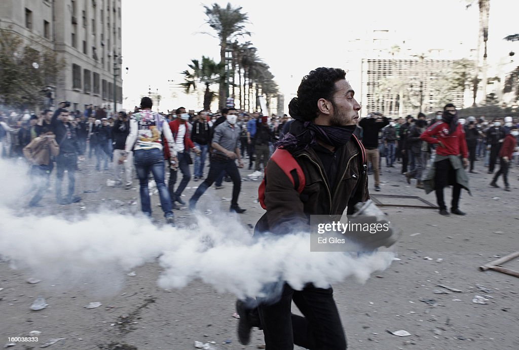 An Egyptian protester runs with a live tear gas canister during clashes with riot police in Tahrir Square on January 25, in Cairo, Egypt. Thousands of protesters converged on the capital's iconic Tahrir Square on Friday to mark the second anniversary of the overthrow of former President Hosni Mubarak's regime. (Photo by Ed Giles/Getty Images).