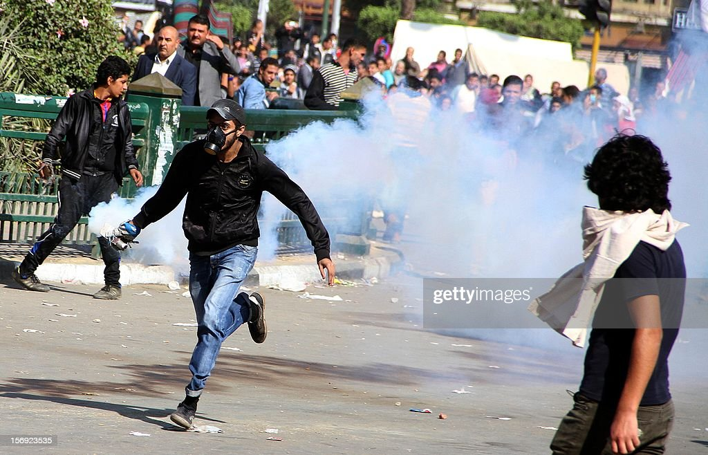 An Egyptian protester runs with a tear gas canister in his hand during clashes with Egytptian riot police in Tahrir square on November 25, 2012 in Cairo. Egypt's powerful Muslim Brotherhood called nationwide demonstrations Sunday in support of Islamist President Mohamed Morsi in his showdown with the judges over the path to a new constitution. AFP PHOTO