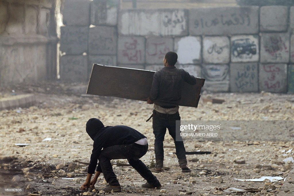 An Egyptian protester shields himself using a piece of metal as a fellow demonstrator collects stones to throw towards riot police during a demonstration in Cairo's Tahrir Square on January 26, 2013. Egypt's Islamist President Mohamed Morsi appealed for calm after at least seven people were killed in violence on the second anniversary of the revolution that ousted Hosni Mubarak.