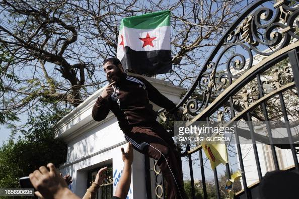 An Egyptian protester shouts slogans after placing a Syrian opposition flag on the gate of the Iranian ambassador's residence in Cairo on April 5...