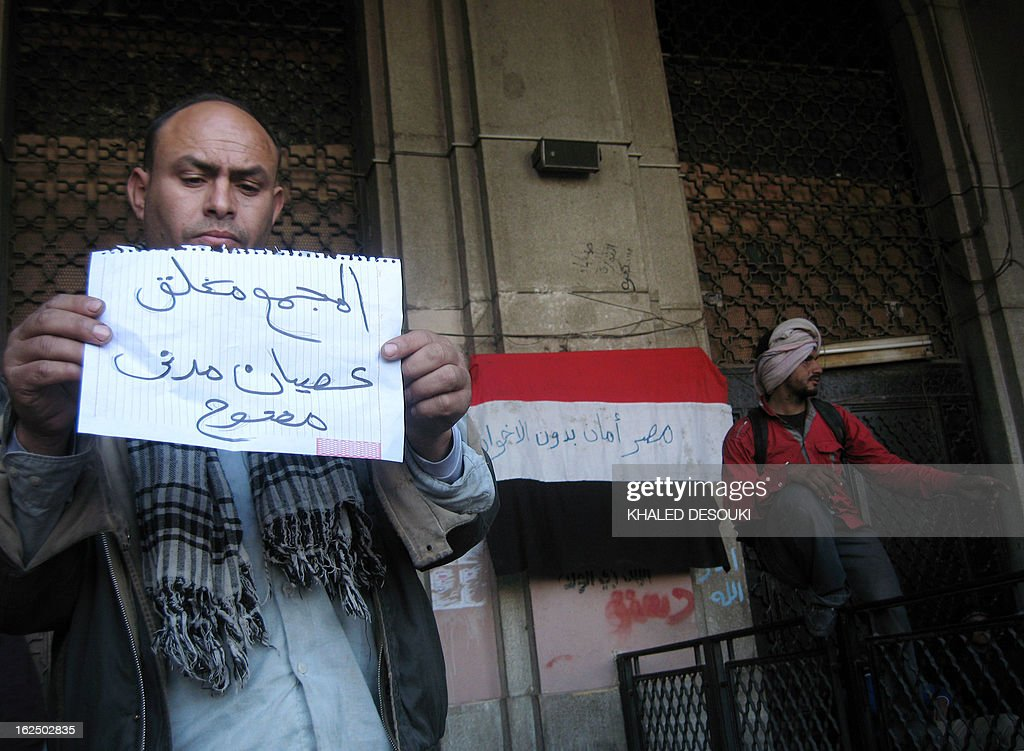 An Egyptian Protester shows a placard reading in Arabic 'The Mugamma is closed, open civil disobedience'' in front of Cairo's main administrative building on February 24, 2013, as they closed its doors part of a growing campaign of civil disobedience around the country. A group of protesters closed the doors of the Mugamma, a massive labyrinth of bureaucratic offices on the edge of Tahrir Square, leaving only a side exit for employees to leave. On the national flag (background) is written 'Egypt is moor safe witout Muslim Brotherhoods''.