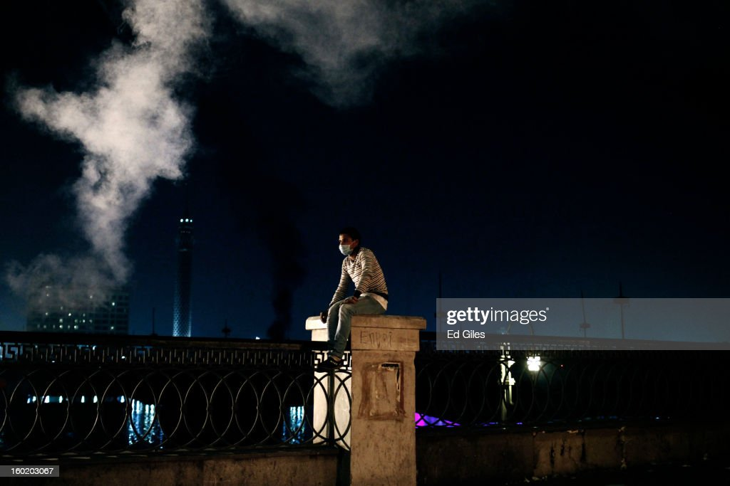 An Egyptian protester sits on a fence underneath a cloud of tear gas during clashes with riot police near Tahrir Square on January 27, 2013 in Cairo, Egypt. Violent protests continued across Egypt two days after the second anniversary of the Egyptian Revolution that overthrew former President Hosni Mubarak on January 25, and one day after the announcement of the death penalty for 21 suspects in connection with a football stadium massacre one year before. The verdict was announced in a case over the deaths of more than seventy fans of Egypt's Al-Ahly football club in a stadium massacre on February 1, 2012, in the northern city of Port Said, during a brawl that began minutes after the final whistle of a match between Al-Ahly and opposing side, Al-Masry. 21 fans of the opposing side, Al-Masry, were given the death penalty, a verdict that must now be approved by Egypt's Grand Mufti. (Photo by Ed Giles/Getty Images).