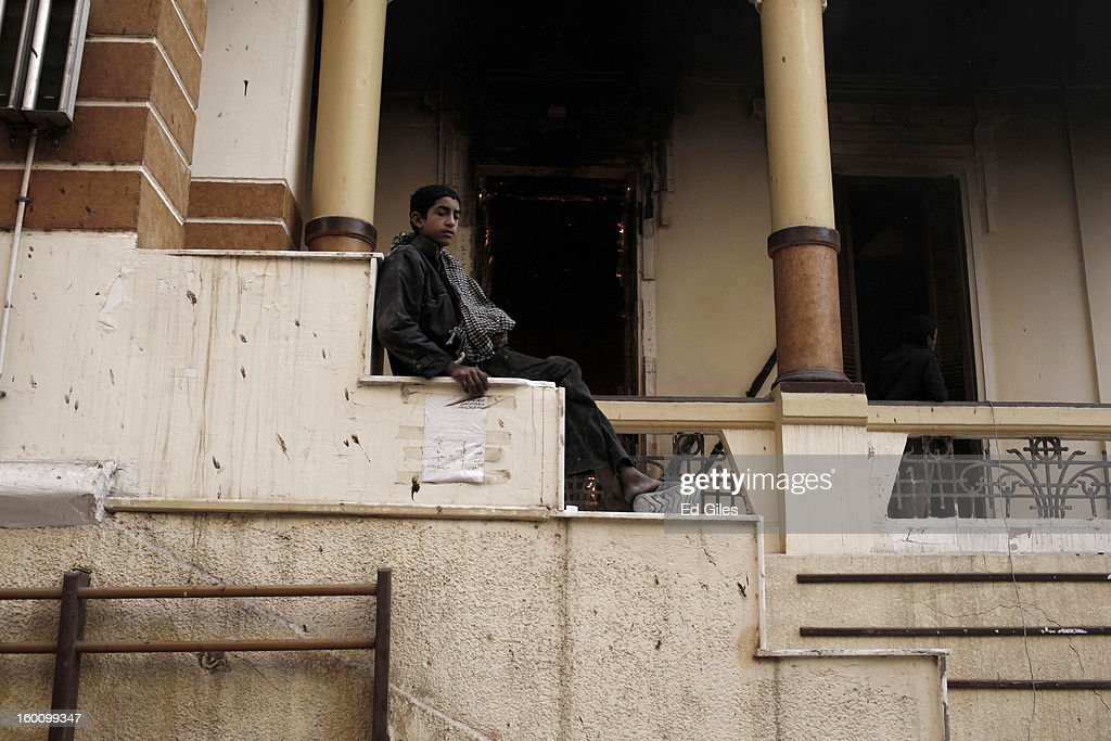 An Egyptian protester sits on the steps of a burning school building during a demonstration following the announcement of the death penalty for 21 suspects in connection with a football stadium massacre last year, on January 26, in Cairo, Egypt. Protests have continued across Egypt after a verdict was announced in a case over the deaths of more than seventy fans of Egypt's Al-Ahly football club in a stadium massacre on February 1, 2012, in the northern city of Port Said, during a brawl that began minutes after the final whistle of a match between Al-Ahly and opposing side, Al-Masry. 21 fans of the opposing side, Al-Masry, were given the death penalty in the court case, a verdict that must now be approved by Egypt's Grand Mufti. The verdict was handed down during a period of high tension across Egypt, one day after the second anniversary of the beginning of Egypt's 2011 revolution that overthrew former President, Hosni Mubarak.