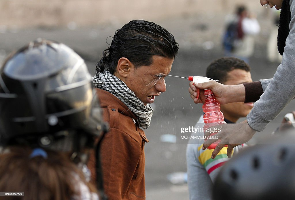 An Egyptian protester sprays water on the eyes of a victim suffering from exposure to tear gas during clashes with riot police near Cairo's Tahrir Square on January 29, 2013. Egypt's military chief warned that the political crisis sweeping the country could lead to the collapse of the state, as thousands defied curfews and the death toll from days of rioting rose to 5.