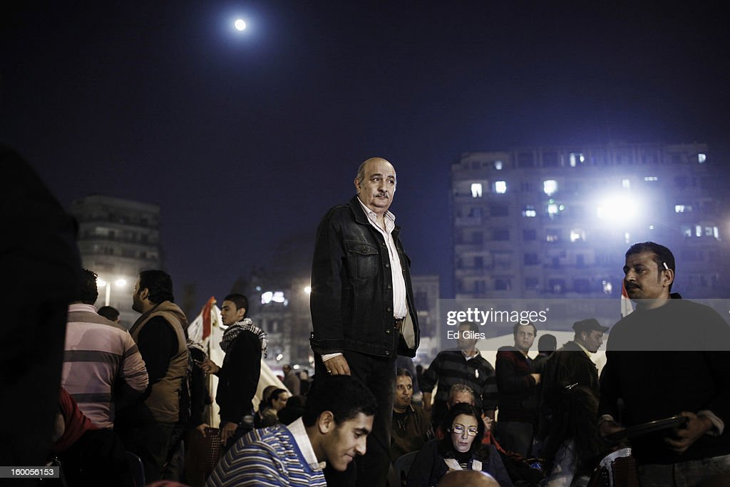 An Egyptian protester stands amongst a crowd during a demonstration in Tahrir Square on January 25, in Cairo, Egypt. Thousands of protesters converged on the capital's iconic Tahrir Square on January 25, to mark the second anniversary of the overthrow of former President Hosni Mubarak's regime. (Photo by Ed Giles/Getty Images).