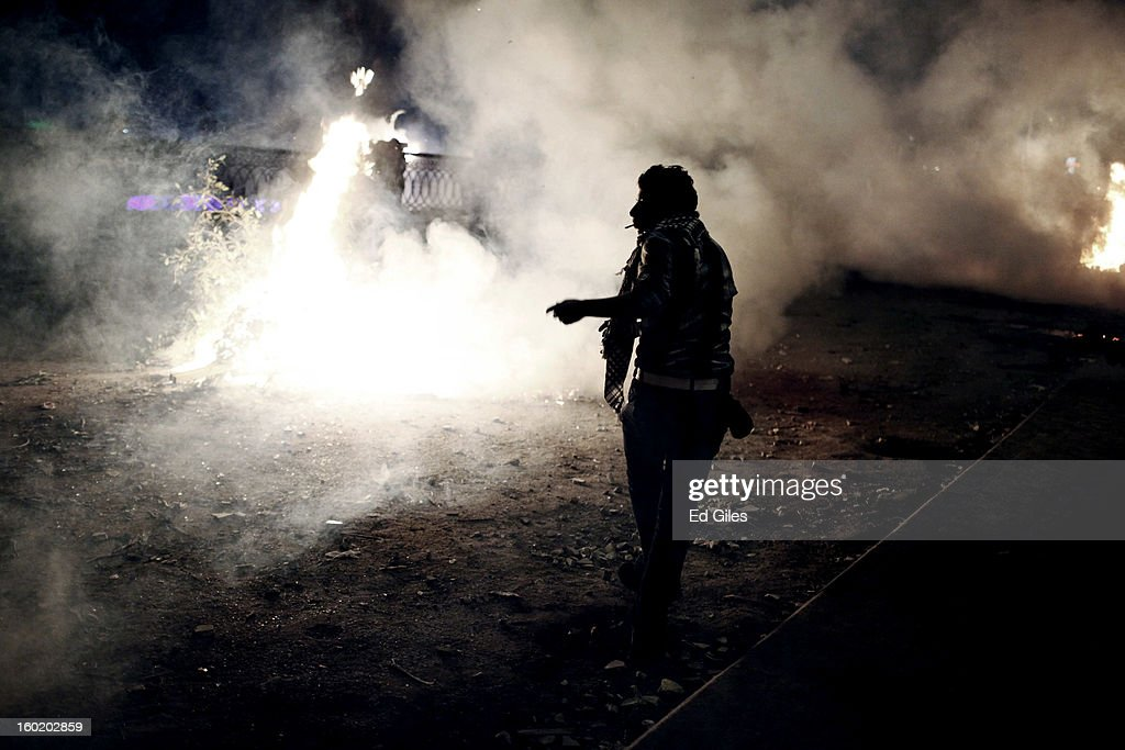 An Egyptian protester stands amongst smoke and tear gas during clashes with riot police near Tahrir Square on January 27, 2013 in Cairo, Egypt. Violent protests continued across Egypt two days after the second anniversary of the Egyptian Revolution that overthrew former President Hosni Mubarak on January 25, and one day after the announcement of the death penalty for 21 suspects in connection with a football stadium massacre one year before. The verdict was announced in a case over the deaths of more than seventy fans of Egypt's Al-Ahly football club in a stadium massacre on February 1, 2012, in the northern city of Port Said, during a brawl that began minutes after the final whistle of a match between Al-Ahly and opposing side, Al-Masry. 21 fans of the opposing side, Al-Masry, were given the death penalty, a verdict that must now be approved by Egypt's Grand Mufti. (Photo by Ed Giles/Getty Images).