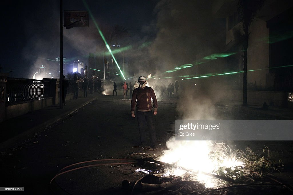 An Egyptian protester stands by a fire lit during clashes with riot police near Tahrir Square on January 27, 2013 in Cairo, Egypt. Violent protests continued across Egypt two days after the second anniversary of the Egyptian Revolution that overthrew former President Hosni Mubarak on January 25, and one day after the announcement of the death penalty for 21 suspects in connection with a football stadium massacre one year before. The verdict was announced in a case over the deaths of more than seventy fans of Egypt's Al-Ahly football club in a stadium massacre on February 1, 2012, in the northern city of Port Said, during a brawl that began minutes after the final whistle of a match between Al-Ahly and opposing side, Al-Masry. 21 fans of the opposing side, Al-Masry, were given the death penalty, a verdict that must now be approved by Egypt's Grand Mufti. (Photo by Ed Giles/Getty Images).