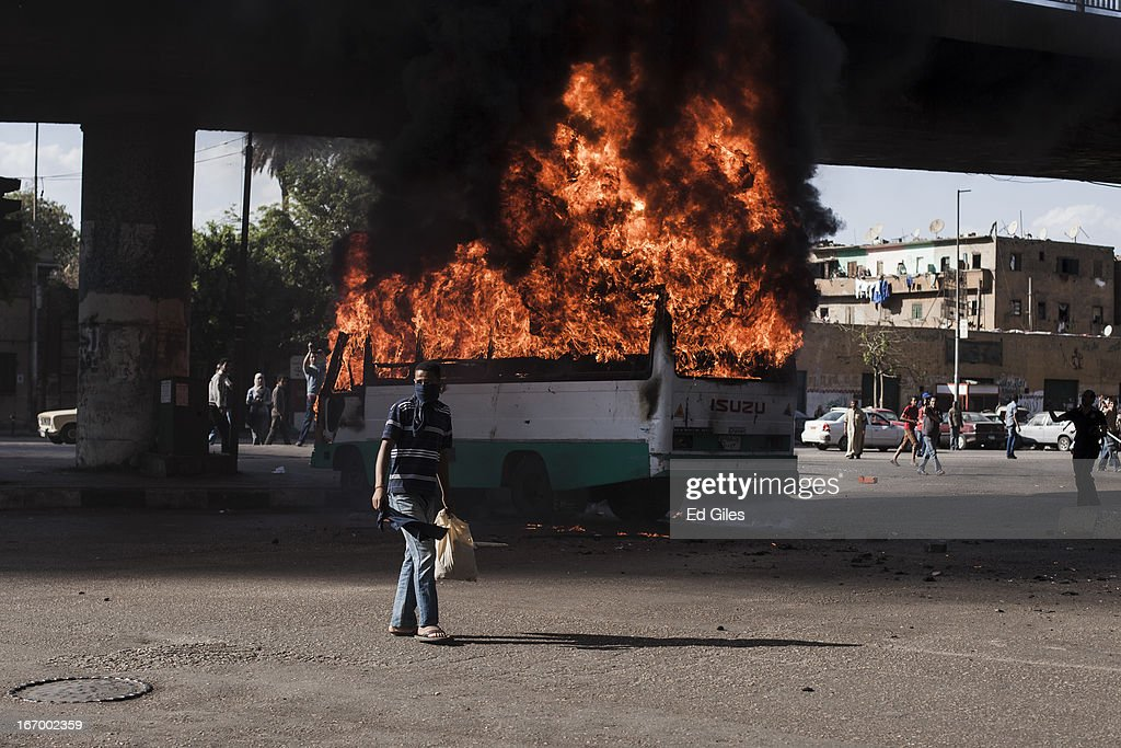 An Egyptian protester stands in front of a burning bus set alight during violent clashes between supporters of Egyptian President Mohammed Morsi and opposition demonstrators on April 19, 2013 in central Cairo, Egypt. Clashes broke out between Islamist protesters and opposition demonstrators, including members of the 'Black Block' - a group of masked protesters who oppose President Morsi and the Muslim Brotherhood - near Tahrir Square on Saturday afternoon. The two groups met after protests by opposing were held in different areas of central Cairo on Friday. (Photo by Ed Giles/Getty Images).