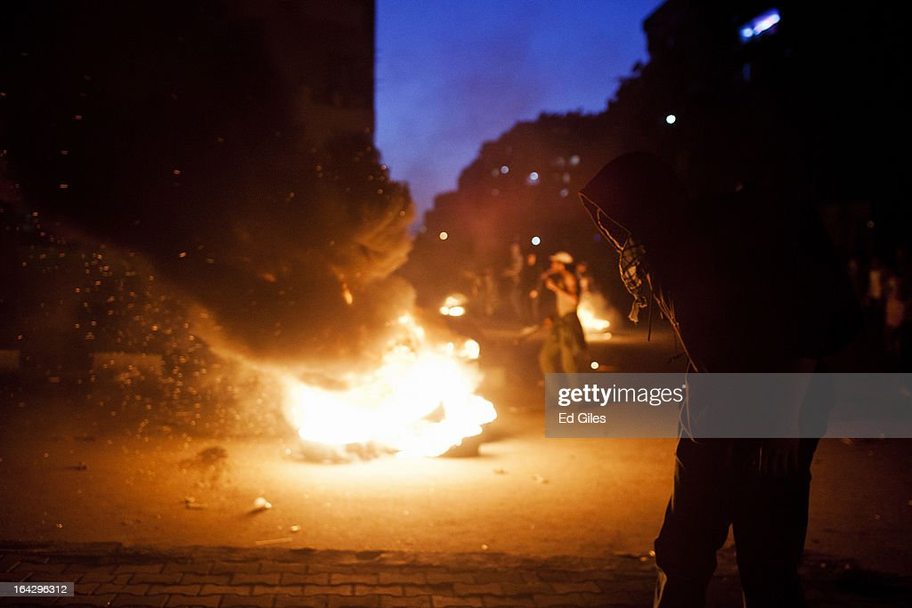 An Egyptian protester stands in front of a burning tire during clashes with Egyptian riot police near the headquarters of the Muslim Brotherhood on March 22, 2013 in Cairo, Egypt. Clashes continued between opposition protesters and both Egyptian security forces and supporters of the Muslim Brotherhood into the night. Opposition demonstrators converged on the headquarters of the Muslim Brotherhood in the Cairo suburb of Muqattam on Friday to protest against the government of President Mohammed Morsi, who is closely connected to the Muslim Brotherhood movement.