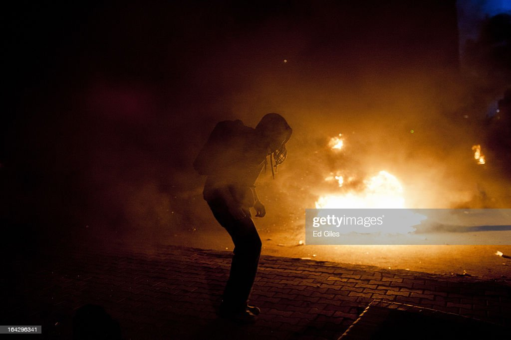 An Egyptian protester stands in front of burning tires during clashes with Egyptian riot police near the headquarters of the Muslim Brotherhood on March 22, 2013 in Cairo, Egypt. Clashes continued between opposition protesters and both Egyptian security forces and supporters of the Muslim Brotherhood into the night. Opposition demonstrators converged on the headquarters of the Muslim Brotherhood in the Cairo suburb of Muqattam on Friday to protest against the government of President Mohammed Morsi, who is closely connected to the Muslim Brotherhood movement.