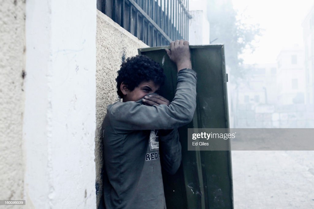 An Egyptian protester suffers from exposure to tear gas fired by Egyptian riot police during a protest following the announcement of the death penalty for 21 suspects in connection with a football stadium massacre last year, on January 26, in Cairo, Egypt. Protests have continued across Egypt after a verdict was announced in a case over the deaths of more than seventy fans of Egypt's Al-Ahly football club in a stadium massacre on February 1, 2012, in the northern city of Port Said, during a brawl that began minutes after the final whistle of a match between Al-Ahly and opposing side, Al-Masry. 21 fans of the opposing side, Al-Masry, were given the death penalty in the court case, a verdict that must now be approved by Egypt's Grand Mufti. The verdict was handed down during a period of high tension across Egypt, one day after the second anniversary of the beginning of Egypt's 2011 revolution that overthrew former President, Hosni Mubarak.