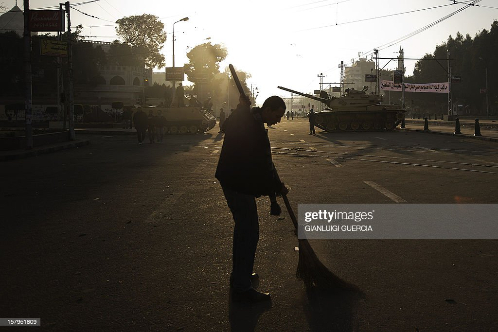 An Egyptian protester sweeps the street near army tanks deployed outside the presidential palace in Cairo on December 8, 2012. The streets of Cairo were calm after a huge but peaceful protest overnight against President Mohamed Morsi, who has greatly expanded his powers and is pushing for disputed constitutional reform. AFP PHOTO/GIANLUIGI GUERCIA