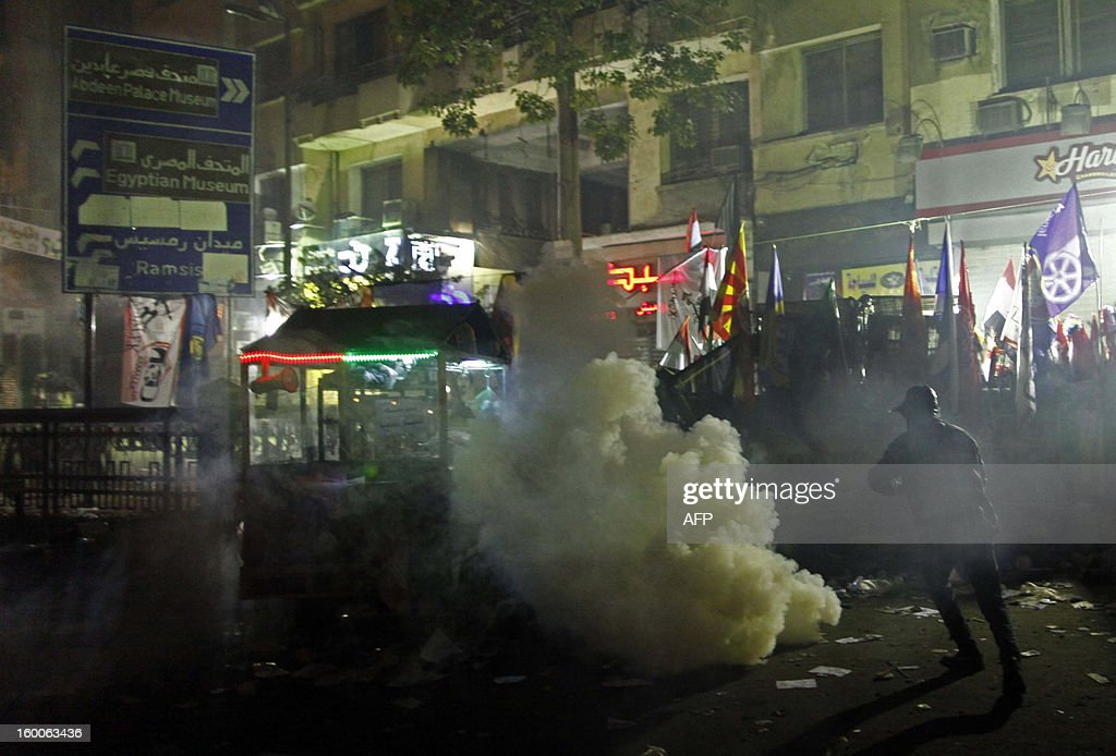 An Egyptian protester takes cover from tear gas fired by riot police in Cairo's Tahrir Square on January 25, 2013. Protesters stormed a regional government headquarters and clashed with police as mass rallies shook Egypt on the second anniversary of a revolt that ousted Hosni Mubarak and brought Islamists to power. AFP PHOTO / MAHMOUD KHALED