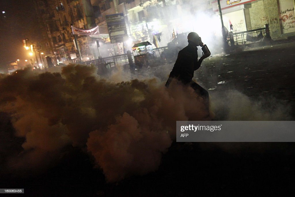 An Egyptian protester takes cover from tear gas fired by riot police in Cairo's Tahrir Square on January 25, 2013. Protesters stormed a regional government headquarters and clashed with police as mass rallies shook Egypt on the second anniversary of a revolt that ousted Hosni Mubarak and brought Islamists to power.