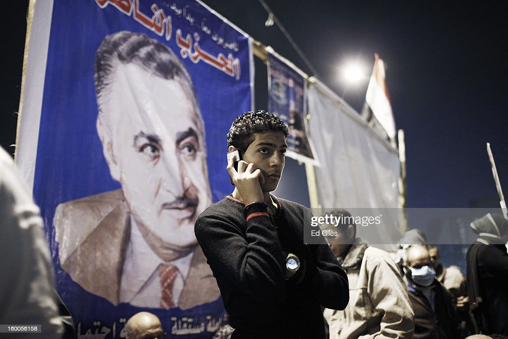 An Egyptian protester talks on a mobile phone standing below a poster of former secular Egyptian President Gamal Abdel Nasser during a demonstration in Tahrir Square on January 25, in Cairo, Egypt. Thousands of protesters converged on the capital's iconic Tahrir Square on January 25, to mark the second anniversary of the overthrow of former President Hosni Mubarak's regime. (Photo by Ed Giles/Getty Images).