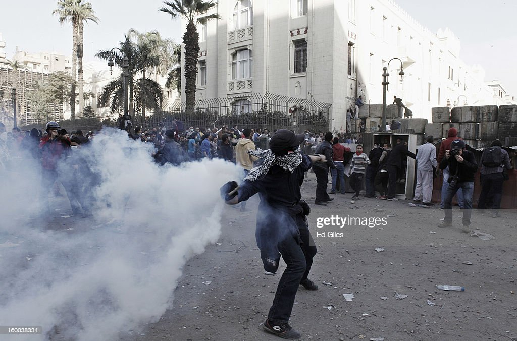 An Egyptian protester throws a live tear gas canister back toward riot police riot police during a demonstration in Tahrir Square on January 25, in Cairo, Egypt. Thousands of protesters converged on the capital's iconic Tahrir Square on Friday to mark the second anniversary of the overthrow of former President Hosni Mubarak's regime. (Photo by Ed Giles/Getty Images).