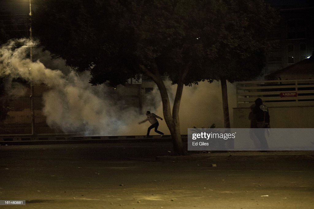 An Egyptian protester throws a live tear gas canister back toward nearby Egyptian riot police during violent protests by the Presidential Palace in Heliopolis, February 11, 2013 in Cairo, Egypt. Protests continued across Egypt against President Morsi and the Muslim Brotherhood on the 2nd anniversary of former President Hosni Mubarak stepping down, and over two weeks after the second anniversary of the Egyptian Revolution beginning on January 25, 2011. (Photo by Ed Giles/Getty Images).