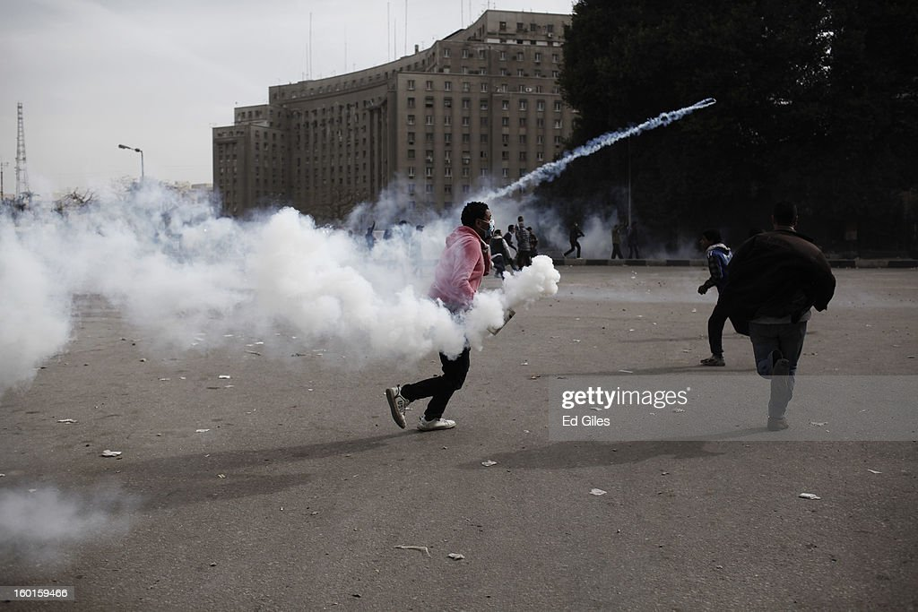 An Egyptian protester throws a live tear gas canister back towards riot police during a demonstration in Tahrir Square on January 27 2013 in Cairo...