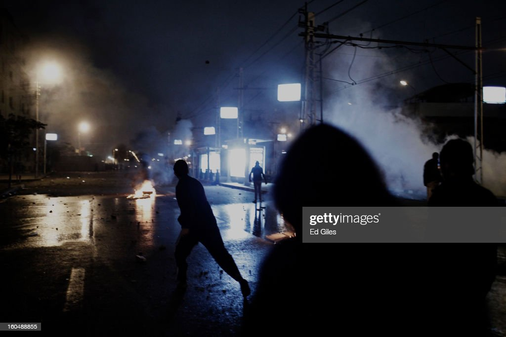 An Egyptian protester throws a live tear gas canister fired by security forces toward Egyptian riot police during clashes outside the Egyptian Presidential Palace in the suburb of Heliopolis on February 1, 2013 in Cairo, Egypt. Protests continued across Egypt nearly one week after the second anniversary of the Egyptian Revolution that overthrew former President Hosni Mubarak on January 25, 2011. Further protests are expected over the weekend to commemorate the first anniversary of the Port Said football massacre, when over 70 fans of the Cairo-based Al Ahly football club were killed in a violent post-match brawl between fans of the opposing teams inside the Port Said football stadium after a match between the Al Ahly and Al Masry football teams.