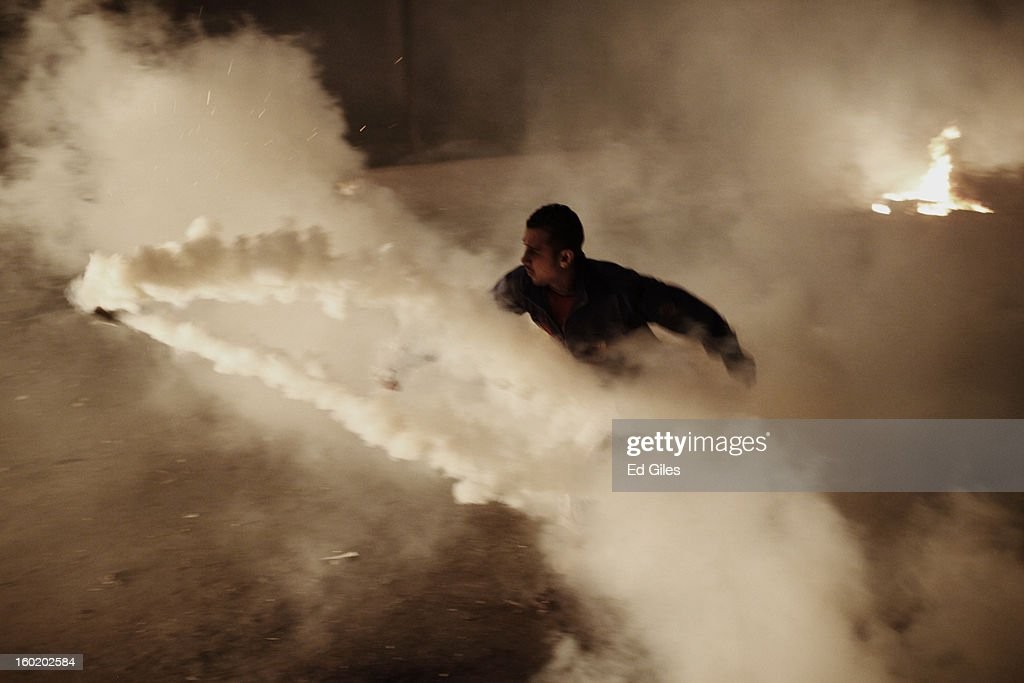 An Egyptian protester throws a live tear gas canister fired by riot police toward a fire during clashes near Tahrir Square on January 27, 2013 in Cairo, Egypt. Violent protests continued across Egypt two days after the second anniversary of the Egyptian Revolution that overthrew former President Hosni Mubarak on January 25, and one day after the announcement of the death penalty for 21 suspects in connection with a football stadium massacre one year before. The verdict was announced in a case over the deaths of more than seventy fans of Egypt's Al-Ahly football club in a stadium massacre on February 1, 2012, in the northern city of Port Said, during a brawl that began minutes after the final whistle of a match between Al-Ahly and opposing side, Al-Masry. 21 fans of the opposing side, Al-Masry, were given the death penalty, a verdict that must now be approved by Egypt's Grand Mufti. (Photo by Ed Giles/Getty Images).