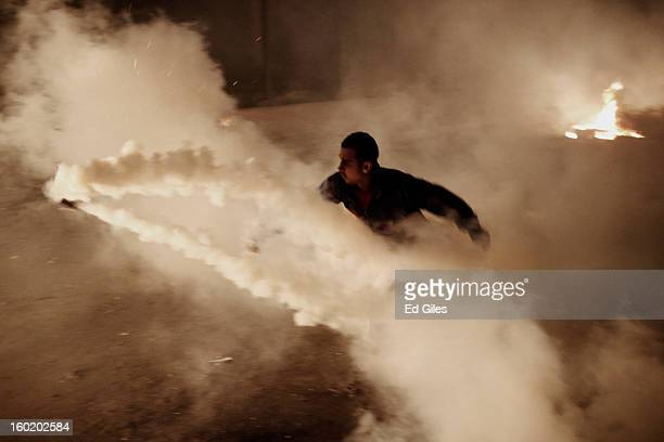 An Egyptian protester throws a live tear gas canister fired by riot police toward a fire during clashes near Tahrir Square on January 27 2013 in...