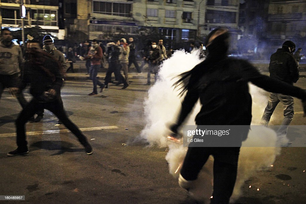 An Egyptian protester throws a live tear gas canister fired by Egyptian riot police during clashes outside the Egyptian Presidential Palace in the suburb of Heliopolis on February 1, 2013 in Cairo, Egypt. Protests continued across Egypt nearly one week after the second anniversary of the Egyptian Revolution that overthrew former President Hosni Mubarak on January 25, 2011. Further protests are expected over the weekend to commemorate the first anniversary of the Port Said football massace, when over 70 fans of the Cairo-based Al Ahly football club were killed in a violent post-match brawl between fans of the opposing teams inside the Port Said football stadium after a match between the Al Ahly and Al Masry football teams. (Photo by Ed Giles/Getty Images).