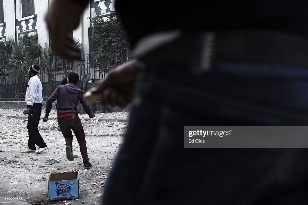 An Egyptian protester throws a rock toward Egyptian riot police during a protest following the announcement of the death penalty for 21 suspects in connection with a football stadium massacre last year, on January 26, in Cairo, Egypt. Protests have continued across Egypt after a verdict was announced in a case over the deaths of more than seventy fans of Egypt's Al-Ahly football club in a stadium massacre on February 1, 2012, in the northern city of Port Said, during a brawl that began minutes after the final whistle of a match between Al-Ahly and opposing side, Al-Masry. 21 fans of the opposing side, Al-Masry, were given the death penalty in the court case, a verdict that must now be approved by Egypt's Grand Mufti. The verdict was handed down during a period of high tension across Egypt, one day after the second anniversary of the beginning of Egypt's 2011 revolution that overthrew former President, Hosni Mubarak.