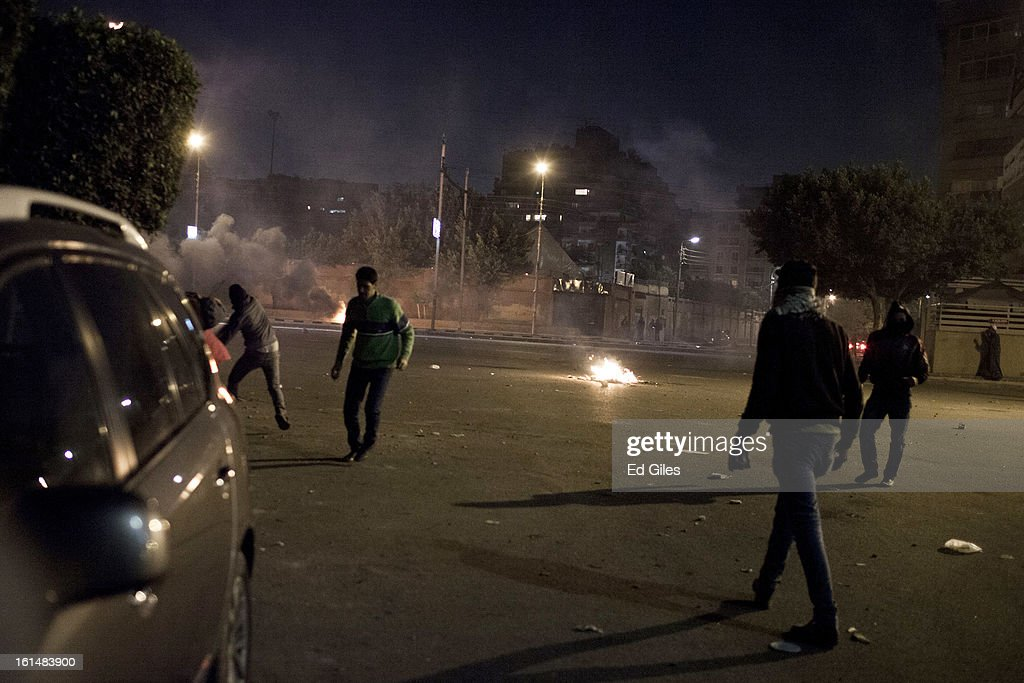 An Egyptian protester throws a rock toward nearby Egyptian riot police during violent protests by the Presidential Palace in Heliopolis, February 11, 2013 in Cairo, Egypt. Protests continued across Egypt against President Morsi and the Muslim Brotherhood on the 2nd anniversary of former President Hosni Mubarak stepping down, and over two weeks after the second anniversary of the Egyptian Revolution beginning on January 25, 2011. (Photo by Ed Giles/Getty Images).