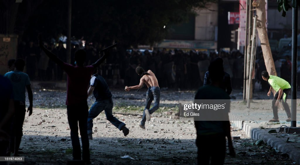 An Egyptian protester throws a rock toward riot police during clashes near the United States Embassy and Tahrir Square on September 14, 2012 in Cairo, Egypt. Over two hundred people have been injured in clashes between protesters and security forces. Protests have continued into a fourth day in central Cairo, with Egyptians demonstrating against a US-made film said to be defaming the Prophet Mohammed, whose trailer had recently been released on Youtube and translated into Arabic. Egyptian authorities began construction of a concrete barrier early Friday morning to stop demonstrations planned across the country for Friday from reaching the US Embassy, after Egyptians demonstrated at the Embassy compound and breached its perimeter walls on Tuesday.