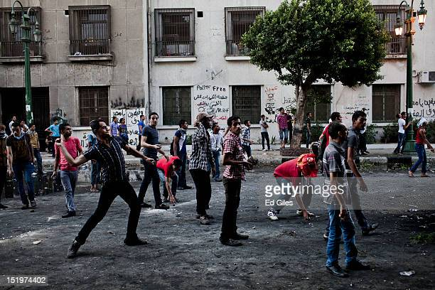 An Egyptian protester throws a rock toward riot police during clashes near the United States Embassy and Tahrir Square on September 14 2012 in Cairo...
