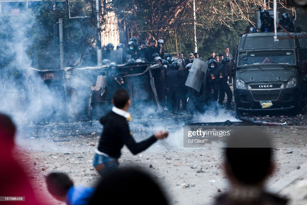 An Egyptian protester throws a rock toward riot police during demonstrations against Egyptian President Mohammed Mursi near Tahrir Square on November 28, 2012 in Cairo, Egypt. Demonstrations have been held after a week of tension and violent protest in response to Egyptian president Mohammed Mursi having awarded himself new constitutional powers, which many believe have been pushed through by the Muslim Brotherhood without inclusive consultation with other members of Egypt's cabinet and political leadership.