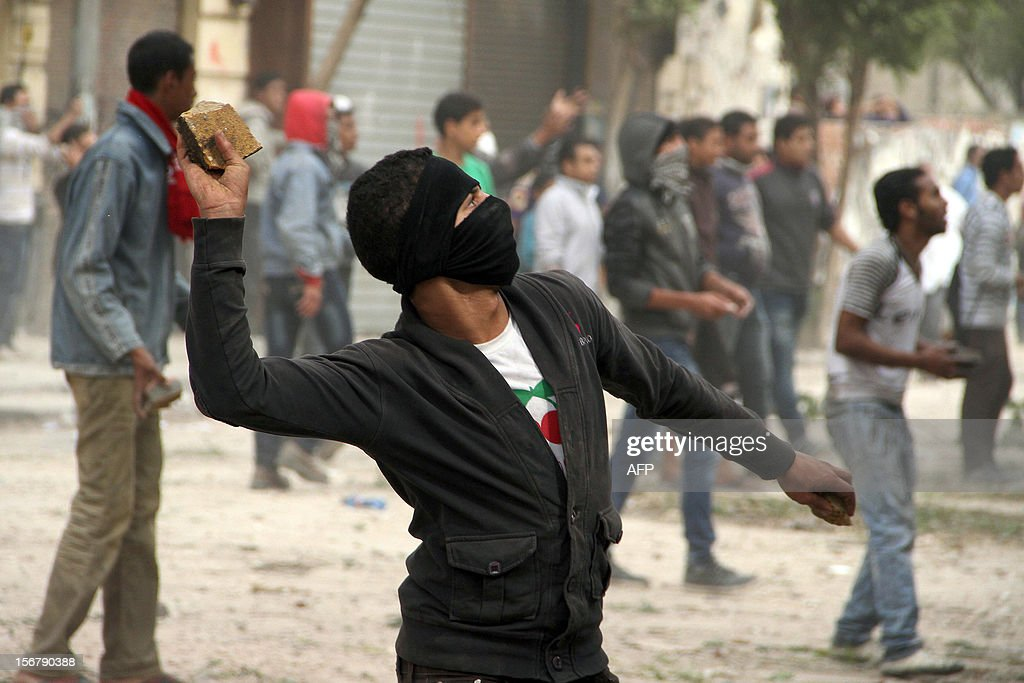 An Egyptian protester throws a stone towards Egyptian security forces during clashes in Cairo on November 21, 2012. Egyptian protesters clashed with police in Cairo for a third day on the one year anniversary of deadly clashes that left 45 dead. At least 45 protesters died in the five days of street battles that began on November 19 last year to put pressure on the military, which took power after a popular uprising overthrew president Hosni Mubarak in February.