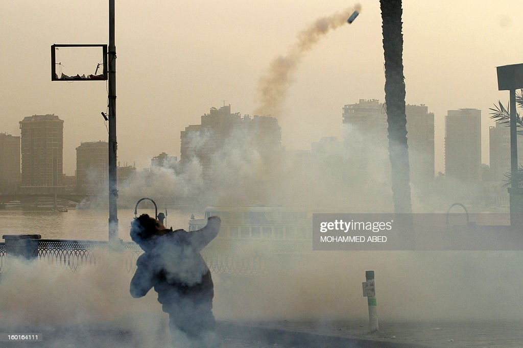 An Egyptian protester throws a tear gas canister at the Nile river during protests near Cairo's Tahrir Square on January 27, 2013. Clashes killed at least 31 people in Egypt's Port Said as violence raged in several cities including the capital following death sentences passed on 21 football fans after a riot.
