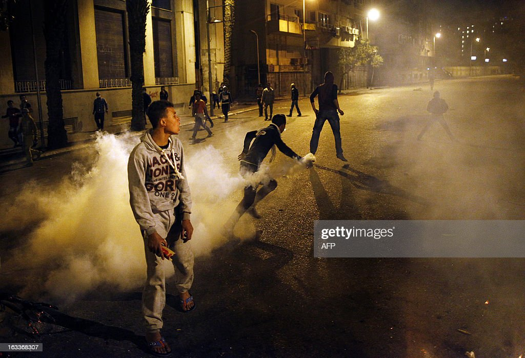 An Egyptian protester throws a tear gas canister back at riot police during clashes in Cairo, on March 8, 2013. Egyptian Interior Minister Mohamed Ibrahim sacked the riot police chief amid strikes by policemen who complained they are ill-equipped to confront protesters, state media reported. AFP PHOTO/MAHMUD KHALED