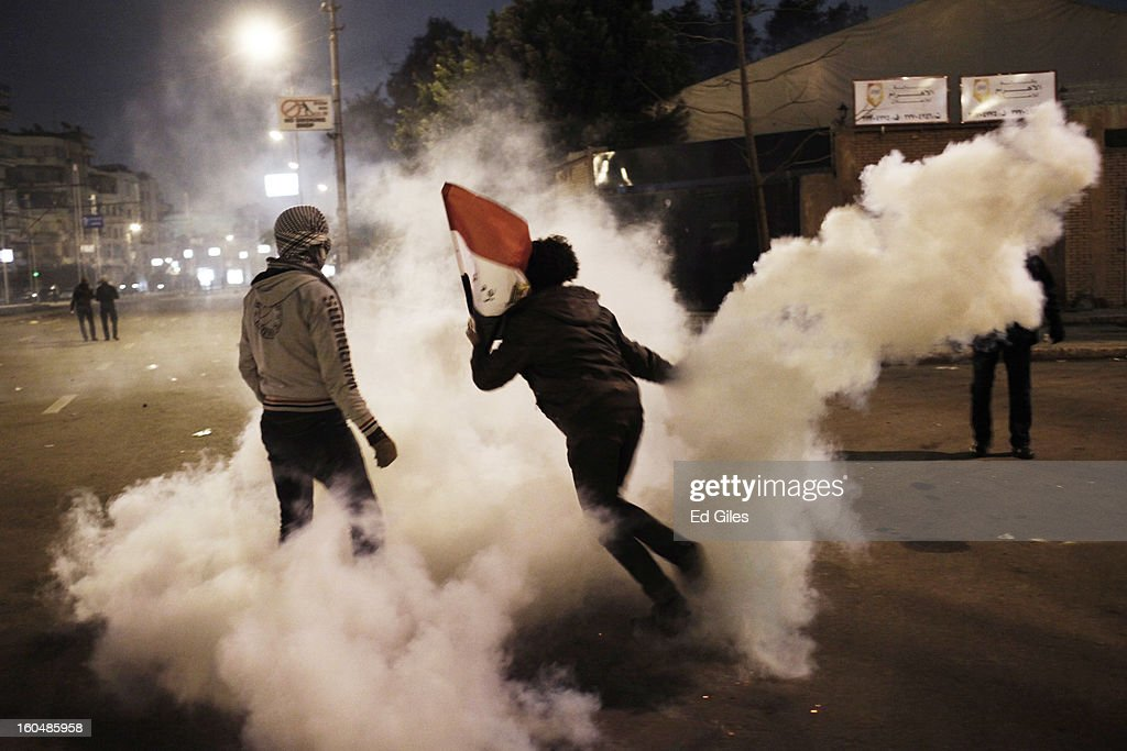 An Egyptian protester throws a tear gas canister fired by security forces toward Egyptian riot police during clashes outside the Egyptian Presidential Palace in the suburb of Heliopolis on February 1, 2013 in Cairo, Egypt. Protests continued across Egypt nearly one week after the second anniversary of the Egyptian Revolution that overthrew former President Hosni Mubarak on January 25, 2011. Further protests are expected over the weekend to commemorate the first anniversary of the Port Said football massace, when over 70 fans of the Cairo-based Al Ahly football club were killed in a violent post-match brawl between fans of the opposing teams inside the Port Said football stadium after a match between the Al Ahly and Al Masry football teams.