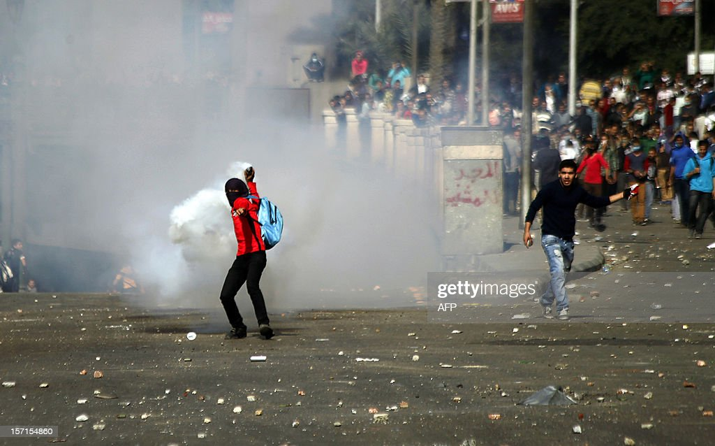 An Egyptian protester throws back a tear gas canister during clash with security forces on November 29, 2012 in Cairo's Tahrir Square, on the third day of protest over President Morsi's decision to grant himself sweeping powers until the new constitution is ratified in a referendum.