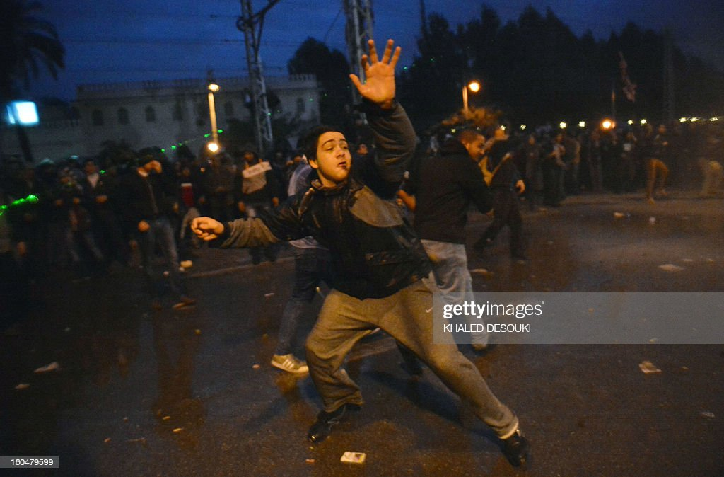 An Egyptian protester throws stones towards the presidential palace in Cairo on February 1, 2013, as thousands of Egyptians flooded the streets in a show of opposition to the Islamist President and his Muslim Brotherhood. Egyptian security used water cannon and fired shots into the air as protesters threw petrol bombs and stones into the grounds of the presidential palace, an AFP correspondent said.