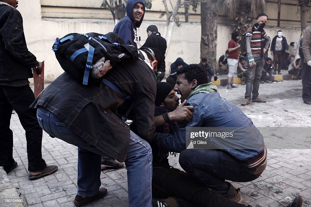 An Egyptian protester tries to carry an injured man away from clashes with Egyptian riot police during a protest following the announcement of the death penalty for 21 suspects in connection with a football stadium massacre last year, on January 26, in Cairo, Egypt. Protests have continued across Egypt after a verdict was announced in a case over the deaths of more than seventy fans of Egypt's Al-Ahly football club in a stadium massacre on February 1, 2012, in the northern city of Port Said, during a brawl that began minutes after the final whistle of a match between Al-Ahly and opposing side, Al-Masry. 21 fans of the opposing side, Al-Masry, were given the death penalty in the court case, a verdict that must now be approved by Egypt's Grand Mufti. The verdict was handed down during a period of high tension across Egypt, one day after the second anniversary of the beginning of Egypt's 2011 revolution that overthrew former President, Hosni Mubarak.