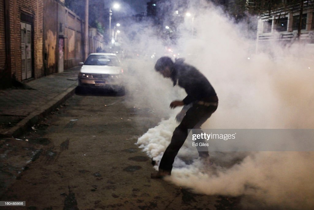 An Egyptian protester tries to pick up a live tear gas canister fired by Egyptian riot police during clashes outside the Egyptian Presidential Palace in the suburb of Heliopolis on February 1, 2013 in Cairo, Egypt. Protests continued across Egypt nearly one week after the second anniversary of the Egyptian Revolution that overthrew former President Hosni Mubarak on January 25, 2011. Further protests are expected over the weekend to commemorate the first anniversary of the Port Said football massace, when over 70 fans of the Cairo-based Al Ahly football club were killed in a violent post-match brawl between fans of the opposing teams inside the Port Said football stadium after a match between the Al Ahly and Al Masry football teams. (Photo by Ed Giles/Getty Images).