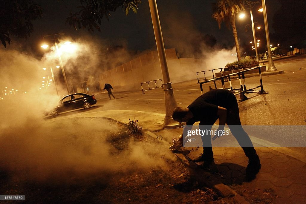 An Egyptian protester tries to throw back a tear gas canister during a demonstration outside the Egyptian presidential palace on December 4, 2012, in Cairo. Tens of thousands of demonstrators encircled the presidential palace after riot police failed to keep them at bay with tear gas, in a growing crisis over President Mohamed Morsi's decree widening his powers.